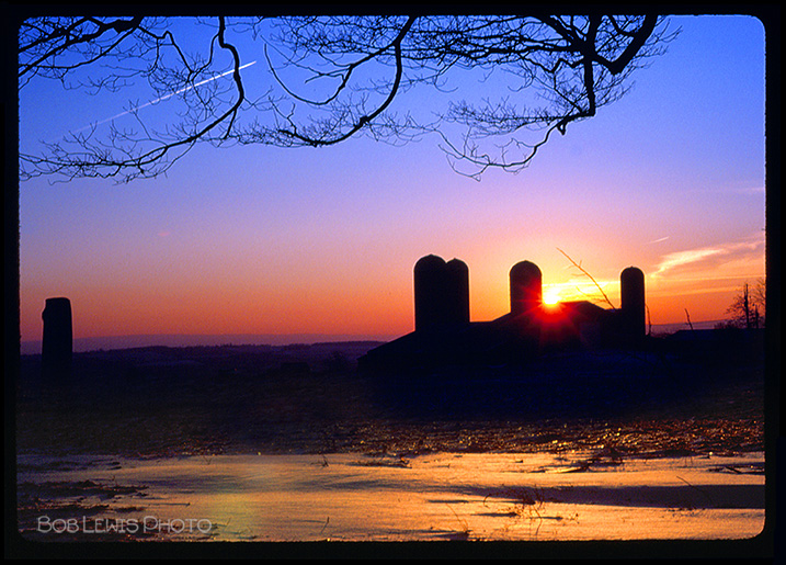 NY state farm with silo at sunset